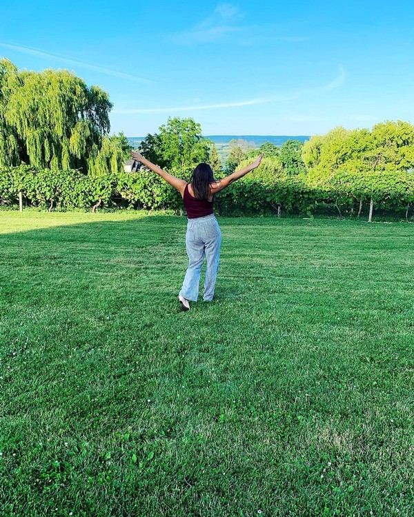 A Glenora guest, arms outstretched, enjoying the view of the willow trees, the vineyard, and Seneca Lake.
