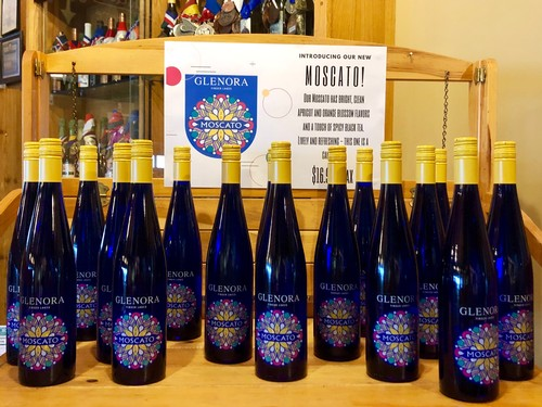 Blue bottles of our 2018 Moscato, capped with yellow, on display in our retail store. The label features a mandala like design in pinks, yellows, greens, and white.