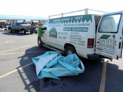A van from Spotts Awning and Tent parked in the Glenora lot.