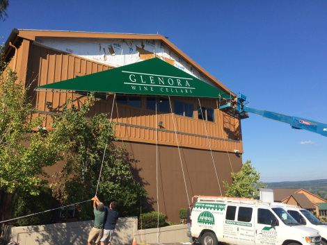 The fresh forest green Glenora sign is being hoisted into place on the facade of the freshly painted building.