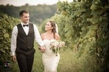 A bride and groom walking through the vineyard in their suit and wedding dress.