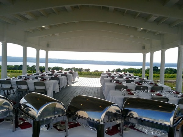 A catered dinner at Boundary Breaks, with white linens, silver buffet service, and a stunning view of Seneca lake