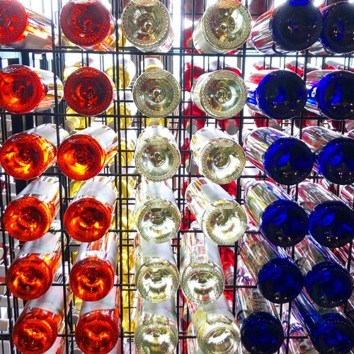 Three types of bottles - one filled with red, one filled with white, and another made of blue glass - lined in a sales rack with the sun streaming through them.