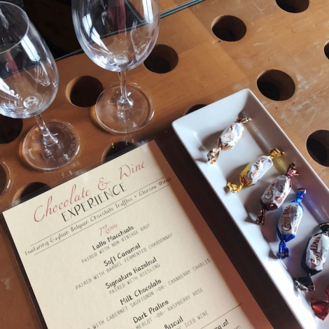 Our chocolate truffles displayed on a platter, alongside wine glasses and our Chocolate & Wine Experience menu